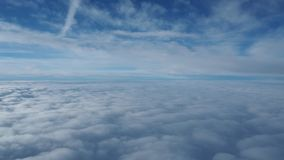 Landscape from the airplane window to a massive sea of clouds in a blue sky. Winter season stock video footage