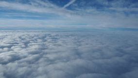 Landscape from the airplane window to a massive sea of clouds in a blue sky.  stock video footage
