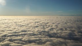 Landscape from the airplane window to a massive sea of clouds in a blue sky Stock Photo