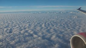 Landscape from the airplane window to a massive sea of clouds in a blue sky Stock Image