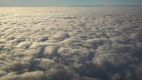 Landscape from the airplane window to a massive sea of clouds in a blue sky Royalty Free Stock Image