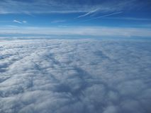 Landscape from the airplane window to a massive sea of clouds in a blue sky Royalty Free Stock Photos