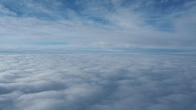 Landscape from the airplane window to a massive sea of clouds in a blue sky. Winter season stock footage