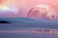 Landscape of an alien planet - huge pink moon reflects in calm o. Cean water. Elements of this image are furnished by NASA Royalty Free Stock Images