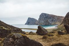 Landscape along the trail from the Kvalvica Beach to the top of the mountain in the Lofoten Islands of Norway. Cloudy stock image