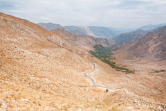 Landscape of the amazing colorful red mountains over the thin curved asphalt road in rocky canyon stock photography