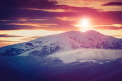 Landscape of amazing evening winter in mountains. Fantastic evening glowing by sunlight. Royalty Free Stock Image