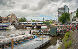Landscape in Amsterdam city with canal bus, boats and pier for tourists near Central Station at summer season Royalty Free Stock Image