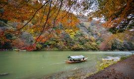 Landscape of Arashiyama in Kyoto, Japan. Kyoto, Japan - Nov 28, 2016. A wooden boat on Hozu River at Arashiyama in Kyoto, Japan. Arashiyama is a nationally Stock Photo