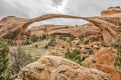 Landscape Arch Against a Cloudy Sky. Landscape Arch on a cloudy day stands out with its beautiful red sandstone colors and green trees to add contrast in Arches Stock Image
