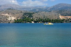 Landscape of Argostoli with blue sea and mountains and with a yellow boats sailing stock images