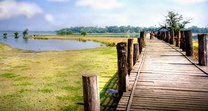 Landscape in asia with a wooden bridge crossing th Royalty Free Stock Image