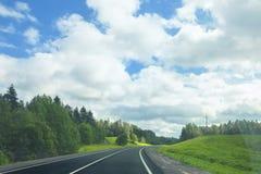 Asphalt road in a sunny summer day. Landscape with an asphalt road in a sunny summer day Stock Image