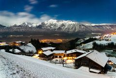 Landscape in Austria. Snowy landscape with traditional village at the Austrian Alps under the moonlight in winter Stock Photos