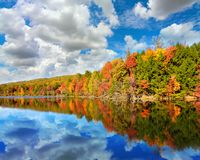 Landscape of autumn colored trees with reflection in Bays Mountain Lake in Kingsport, Tennessee. Tranquil natural landscape of Tennessee woodland forests in full Royalty Free Stock Images
