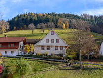 Landscape of autumn countryside with wooden farmhouses green hill and rugged mountains in the background ~ Idyllic view of vill Stock Images