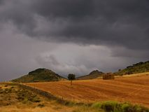 Landscape with bales of straw. Under threatening storm sky royalty free stock photo