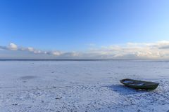 The coast of Baltic sea. Landscape landscape of the Baltic Sea coast in winter with beautiful clouds and blue sky on a sunny day, water and stones, covered with Royalty Free Stock Photos