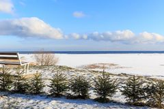 The coast of Baltic sea. Landscape Baltic Sea coast in winter with beautiful clouds and blue sky on sunny day, water and stones, covered with snow and ice. Bench Stock Images