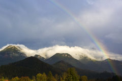 Landscape of Bavarian mountains with rainbow. And fog Royalty Free Stock Image