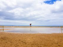 Landscape of beach and sea with lifeguard post and green vandera allowing the bath. Canary Islands, Spain. Water tracks morning wet sky surf nature tropical royalty free stock images