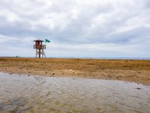 Landscape of beach and sea with lifeguard post and green vandera allowing the bath. Canary Islands, Spain. Water tracks morning wet sky surf nature tropical stock photography