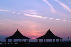 Landscape with beach umbrellas in the sunset. Sunset landscape with beach umbrellas in front of the sea Royalty Free Stock Photos