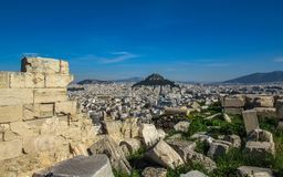 Athens from Acropolis showing ruins in a foreground and Mount Lycabettus surrounded by white buildings and blue sky stock photos