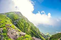 Landscape breathtaking view of a valley from a high mountain at cloud level on a sunny day stock images