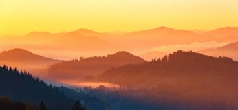 Landscape with beautiful mountains, fields and forests covered with morning fog. Panorama with interesting sunrise. Autumn. royalty free stock photos