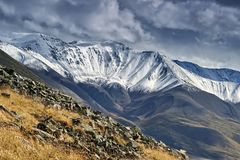 Landscape beautiful snow-covered mountain peaks. Under the bright sun and gloomy clouds Stock Images