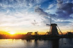 Landscape with beautiful traditional Dutch mill near water courses with fantastic sunset and reflection in water. Netherlands. Royalty Free Stock Images