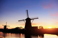 Landscape with beautiful traditional Dutch mill near water courses with fantastic sunset and reflection in water. Netherlands. Royalty Free Stock Photo