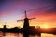 Landscape with beautiful traditional Dutch mill near water courses with fantastic sunset and reflection in water. Netherlands. Royalty Free Stock Photos