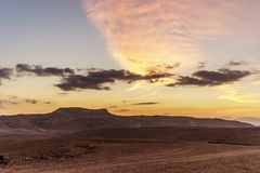 Landscape of beautiful yellow sunrise. View on nature of negev desert in israel. Colorful clouds sun sand and rocks in national amazing park. Morning travel Royalty Free Stock Photo