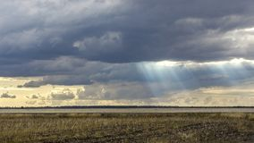 Landscape with big wheat field. weather change. Sun rays Royalty Free Stock Images
