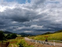 Landscape with biker. And rain sky threatening royalty free stock images