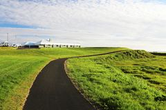 Landscape with black asphalt road going through green meadows. Beuutiful blue sky on background. Summer scenic landscape Stock Images