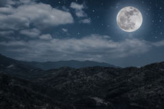 Landscape of blue dark night sky with many stars and cloudy. Landscape of night sky with many stars and cloudy above mountain peak. Beautiful bright super moon Royalty Free Stock Photos