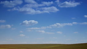 Landscape blue sky with clouds running over the field. Horizon of the field, shot from a distance. Accelerated video the day is ov stock footage