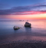 Landscape with blue water, stones and colorful sky Stock Photo