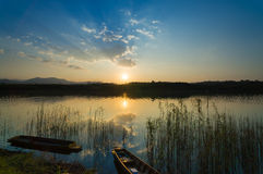 Landscape with boat and dramatic sunset with dense grasses Stock Image