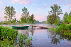 Landscape with boat and footbridge on the river. Rural landscape with boat and footbridge on the Narew river after fog, Poland royalty free stock image