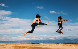 Landscape with boy and girl jumping high Stock Images