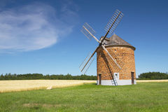 Landscape with a brick windmill Stock Photos