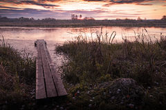 Landscape with a bridge in the foreground. At sunrise in purple colors Royalty Free Stock Images