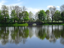 Landscape with a bridge and a pond Stock Images