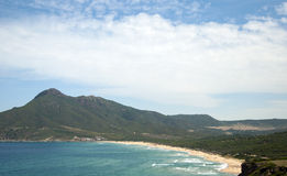 Landscape of Bugerru's coastline in Sardinia, with a cloudy blue. Sky, mountain, the beach and a rough sea for tourism royalty free stock photos