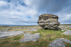 Landscape of Burren. Huge limestone glacial erratic boulder on the cliffs in Doolins Bay, The Burren, County Clare, Ireland Royalty Free Stock Photography