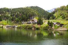 Landscape with cabins near a mountain lake Stock Photos
